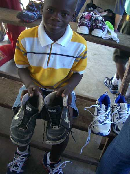 by: CONTRIBUTED PHOTO: BCC - A Haitian boy is all smiles as he shows off his new shoes while displaying the old ones.