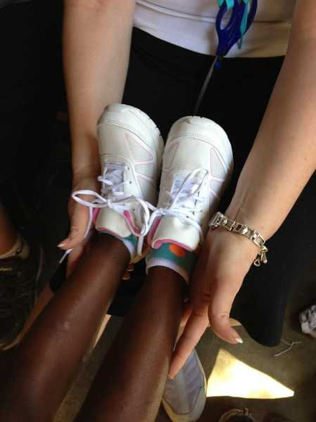 by: CONTRIBUTED PHOTO: BCC - A new pair of shoes is placed on the feet of a young Haitian girl.