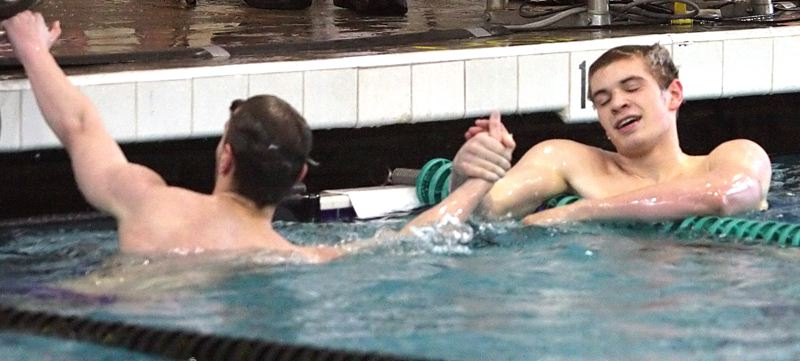 by: MILES VANCE - FAST FRIENDS - Sunset's Jonathan Zoucha (right) shakes hands with teammate Cameron Stitt after Zoucha broke Stitt's Metro League record in winning the 200-yard freestyle race at Saturday's Metro League District Meet at Tualatin Hills Aquatic Center.