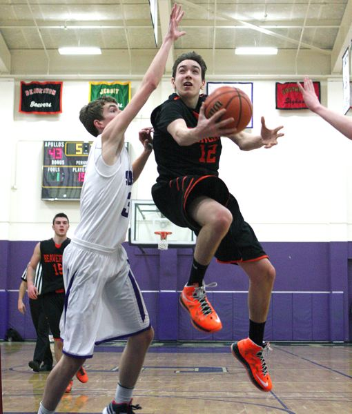 by: MILES VANCE - AT THE BASKET - Beaverton's Ty Peacock leaps past Sunset's Jonathan Willes during his team's Tuesday win at Sunset High School.