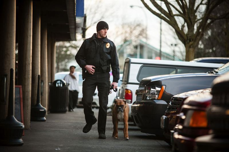 by: TRIBUNE PHOTO: CHRISTOPHER ONSTOTT - Chris Huskey and his drug sniffing dog Riley keep an eye on the lottery row strip mall on Hayden Island for suspicious activity. Neighbors and police are cranking up the pressure on the Lottery Row owners.