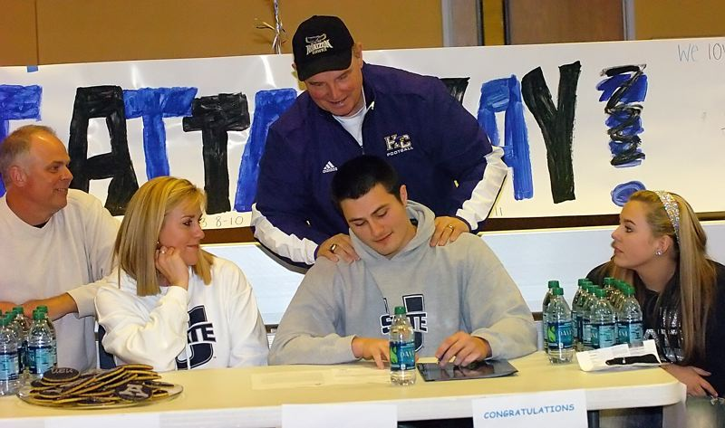 by: DAN BROOD - ON THE DOTTED LINE -- Horizon Christian senior Wyatt Houston, with his parents, siblings and Hawks football coach George Crace by his side, signs a letter of intent to play college football at Utah State.