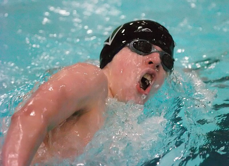 by: DAN BROOD - UP FOR AIR -- Tigard freshman Kyle Miller takes a breath during the 500-yard freestyle event at the Pacific Conference district championships. Miller advanced to the state meet in two events.
