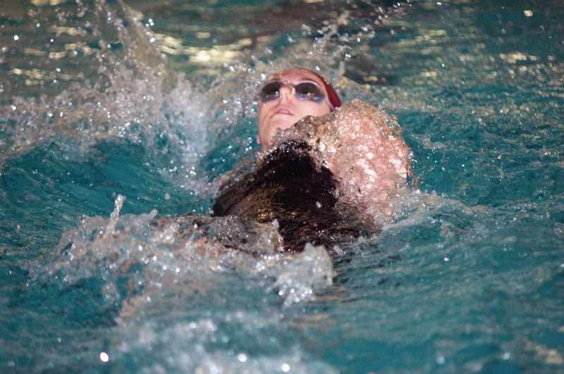 by: PARKER LEE - RECORD BREAKER -- Sherwood High School senior Emily Stevens set a new school record with her winning time of 58.52 seconds in the 100-yard backstroke event Saturday at the Northwest Oregon Conference District Swim Championships held at the Parkrose Aquatic Center.