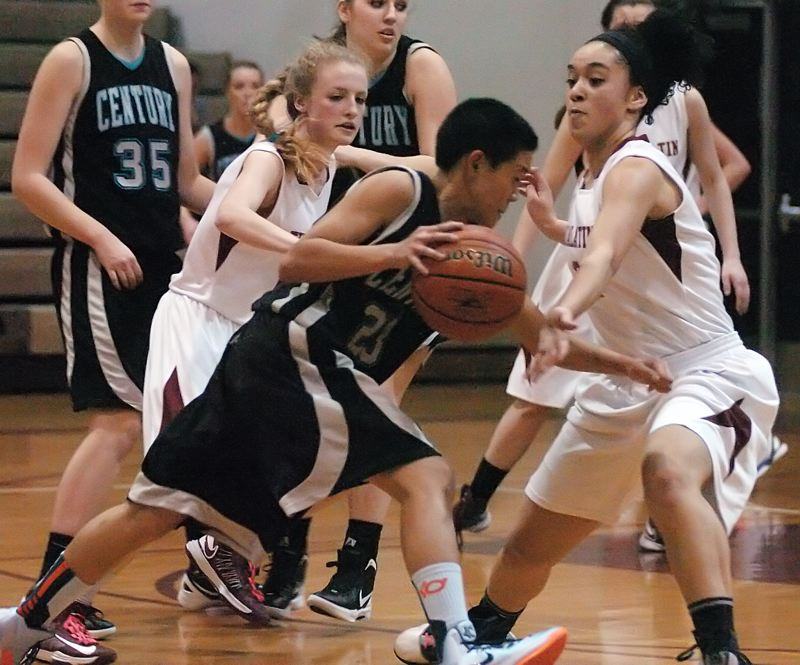 by: DAN BROOD - DOUBLE TEAMED -- Tualatin senior Britta Hall (left) and junior Jasmine Miller trap Century freshman guard Jade Bevandich during the second half of Tuesday's game. The Timberwolves won 70-51.
