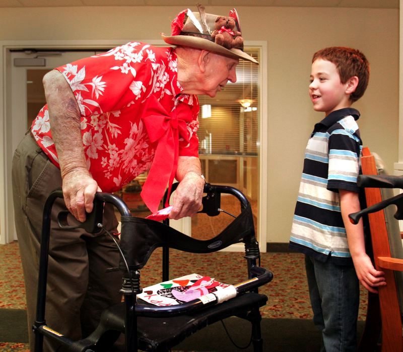 by: OUTLOOK PHOTO: JIM CLARK - Sweetbriar Elementary first-grader Samuel Moffit talks with 96-year-old Cherry Park Plaza resident Roger Lowe after presenting him with a valentine.