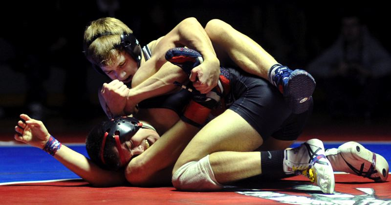by: JOHN LARIVIERE - Oregon City senior Kyle Sether ties himself in a knot as he rides David Douglas senior Jeramiah Baker in the 126-pound final of last weekends Three Rivers League/Mt. Hood Conference Regional Tournament.