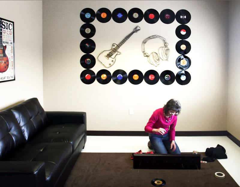 by: OUTLOOK PHOTO: JIM CLARK - Volunteer Dorcas Mason works on a piece of artwork that will utilize old records for a music-themed room at the remodeled DHS building in Gresham on Monday, Feb. 18. The remodel included paint, wall art, murals and new furniture.