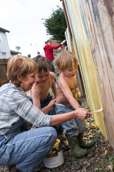 by: NEWS-TIMES PHOTO: CHASE ALLGOOD - Donna VanDyke helps her grandsons, Jonathan Nemeyer and Benjamin Nemeyer, master the fine art of painting over a graffiti-marred fence.