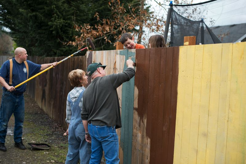 by: NEWS-TIMES PHOTO: CHASE ALLGOOD - Forest Grove Fire Marshal Dave Nemeyer (left, with roller) and his son Benjamin, 2, paint over graffiti that marred an alleyway fence behind the familys B Street home last week.