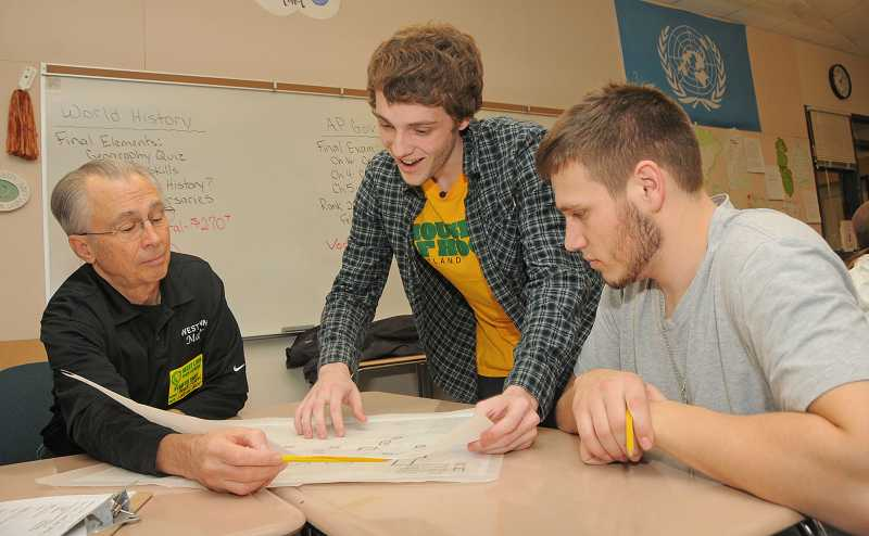 by: VERN UYETAKE  - West Linn High School students Jimmy Donnelly, center, and Marcus Campbell present their plan to West Linn Mayor John Kovash.