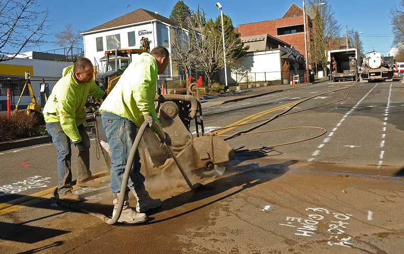 by: VERN UYETAKE - Guy Gibbons, left, and Benjamin Ickes of A Cut Above cement cutters begin the process of removing pavement. Construction crews bgean working on Second Street on Tuesday. The city plans to repair the deteriorating roadway and make other improvements.
