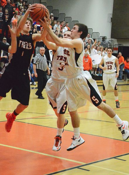 by: JOHN BREWINGTON - Scappoose's Kyle Kramer (21) and Zach Smith (3) grapple for a rebound with Yamhill-Carlton's Landon Heryford during last Tuesday's game. The Indians won the contest and clinched the Cowapa League title.