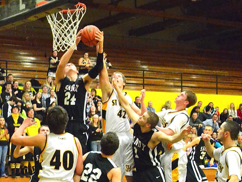 by: PAMPLIN MEDIA GROUP: JOHN BREWINGTON - Sandy center Justin Adams goes above a crowd to pull down a rebound during Tuesday nights win at St. Helens.