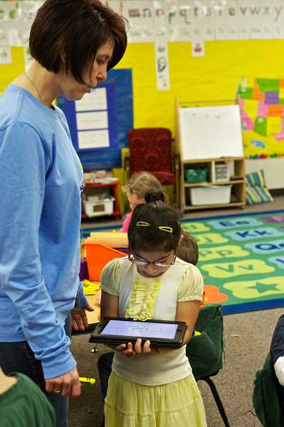 by: TIMES PHOTO: JAIME VALDEZ - Durham Elementary School kindergarten teacher Leslie Kolb helps Brenda Colorado with a project on her iPad.