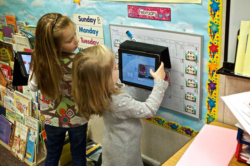 by: TIMES PHOTO: JAIME VALDEZ - Kindergartners Kaylee Smith and Sammy Mudd scan a code as part of an assignment in Leslie Kolbs class at Durham Elementary School. IPads are a part of life in the school and are used to teach reading and writing.