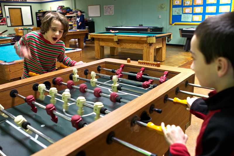 by: TIMES PHOTO: JAIME VALDEZ -  Luke Loomis, 8, and Dakoda Robedeau, 9, play foosball at the Beaverton Police Activities League Clubhouse.