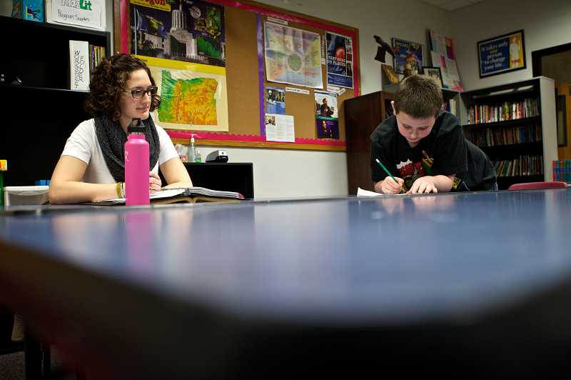 by: TIMES PHOTO: JAIME VALDEZ - Gretchen Young, who is the educational coordinator at the Beaverton Police Activities League center, watches Landon Ashcraft, 9, work on his math homework.