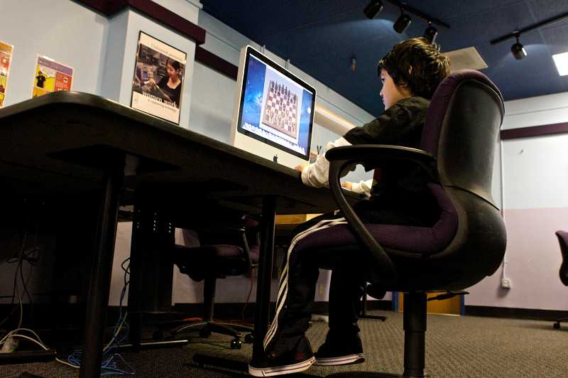 by: TIMES PHOTO: JAIME VALDEZ - Sam Loredo, 10, plays chess on a computer at the Beaverton Police Activities League center.