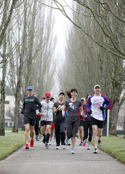 by: TIMES PHOTO: JONATHAN HOUSE - A group of volunteer coaches for Portland Fit get charged up for the upcoming marathon training season with a Saturday morning run on the Fanno Creek Trail near the club's new home base at Portland Running Company.