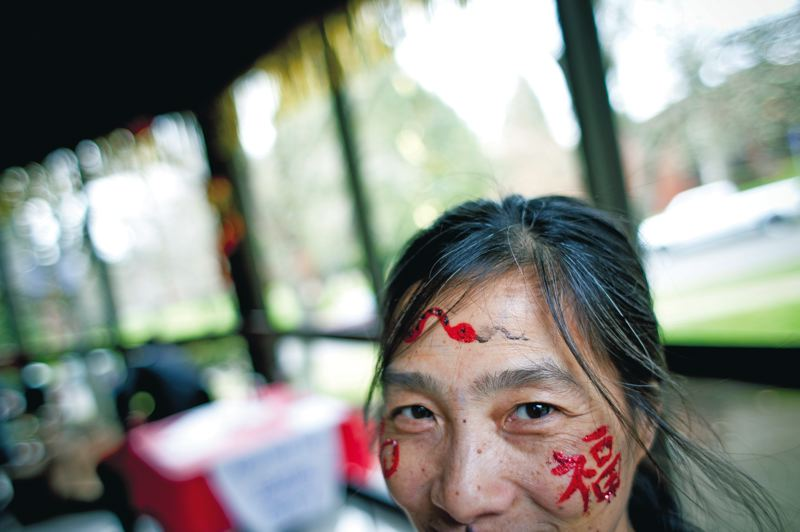 by: TRIBUNE PHOTO: CHRISTOPHER ONSTOTT - With 'prosperity' painted on her face in Chinese, volunteer Khah Nguyen welcomes guests to Portland Community College's Year of the Snake celebration Monday, held at Warner Pacific College's McGuire Auditorium in Southeast Portland.