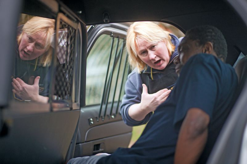 by: TRIBUNE PHOTO: CHRIS ONSTOTT - Portland police officer Bridget Sickon prepares to take sex offender Stanley Washington to jail for failing to re-register after changing his address.