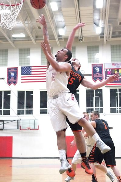 by: MILES VANCE - HE SCORES - Westview senior Dyrall Goods leaps past Beaverton senior Joey Losk to score during his team's Tuesday home win.