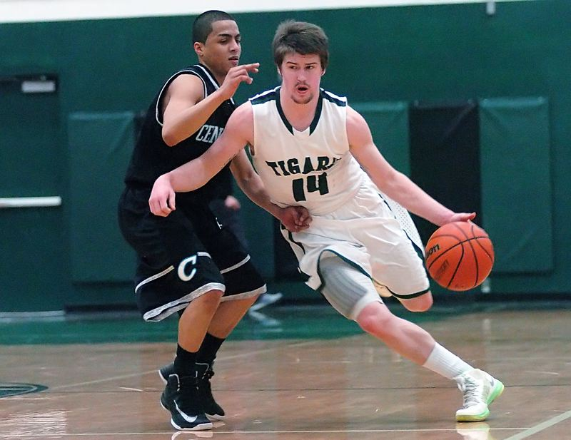 by: DAN BROOD - DRIBBLE DRIVE -- Tigard senior Evan Garrison (right) looks to drive past Century's Jamel Liggins in Tuesday's game.