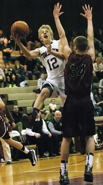 by: DAN BROOD - HIGH FLYER -- Tualatin senior guard Jon Fishback (left) goes flying up to the basket against Glencoe's Kyle Mincemoyer during Fridays game. The Wolves scored a 94-74 victory.