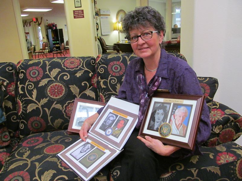 by: PHOTO BY ELLEN SPITALERI - Myra Mathews, co-manager of Somerset Lodge in Gladstone, displays the book of honor and several photos for the new wall honoring veterans.