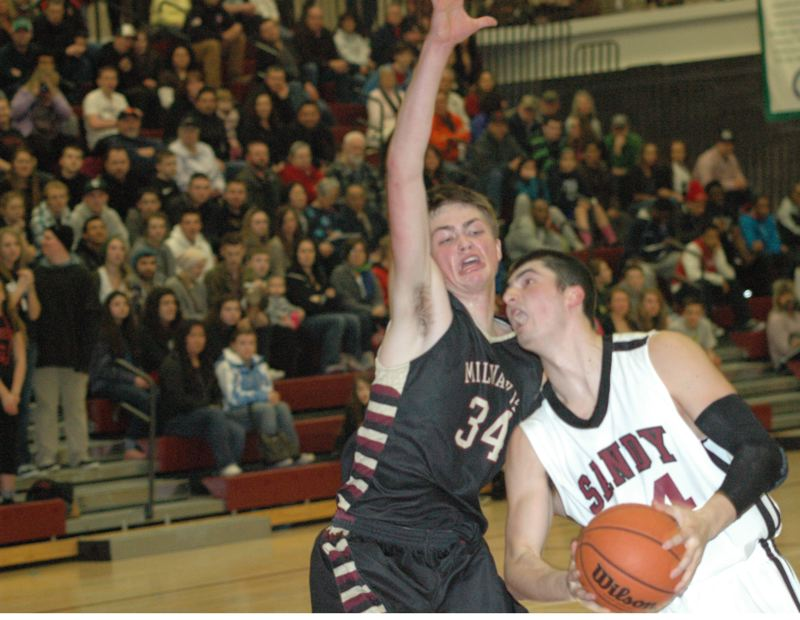 by: PARKER LEE - Milwaukie 6-9 senior post Henry Morris (34) tells Sandy offensive star Justin Adams not on my watch in last weeks boys basketball victory at Sandy.