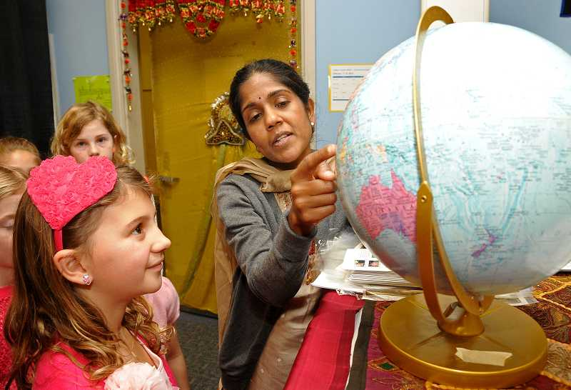 by: VERN UYETAKE - Third-grader Talya Clopton learns about where India is on the globe from parent Gayathri Iyer.