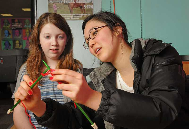 by: VERN UYETAKE - Jini Stupak shares her expertise on knitting with Lindsay McDowell during a class at McKenzie Teen Lounge.