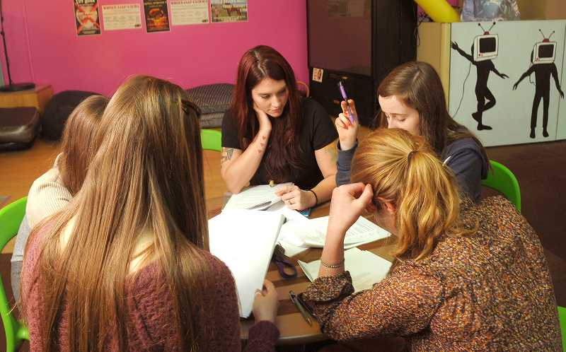 by: VERN UYETAKE - Cydny Winslow, teen program director for the city of Lake Oswego, gets right in the middle of a group of girls doing their homework at Teen Lounge.