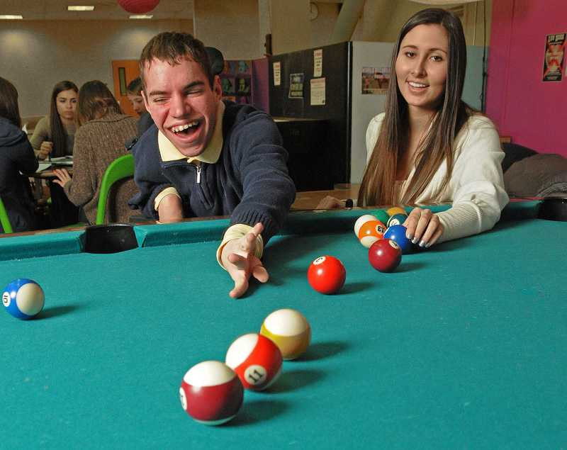 by: VERN UYETAKE - Adam Goeken and Torrie White laugh it up while playing pool. Both teens are big reasons the Teen Lounge has grown so much in recent years.