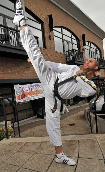 by: VERN UYETAKE - Master Frenel Ostin displays his black belt form right in front of his new One Taekwondo Academy in West Linn.