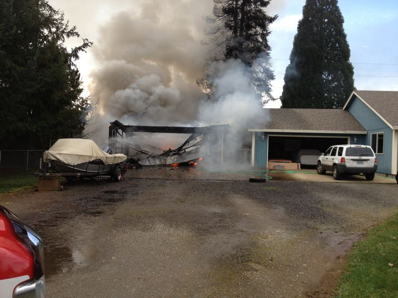 by: PHOTO COURTESY: CLACKAMAS FIRE DISTRICT NO. 1 -  Clackamas Fire District No. 1 crews extiguish this garage fire before it spread to the next-door house.