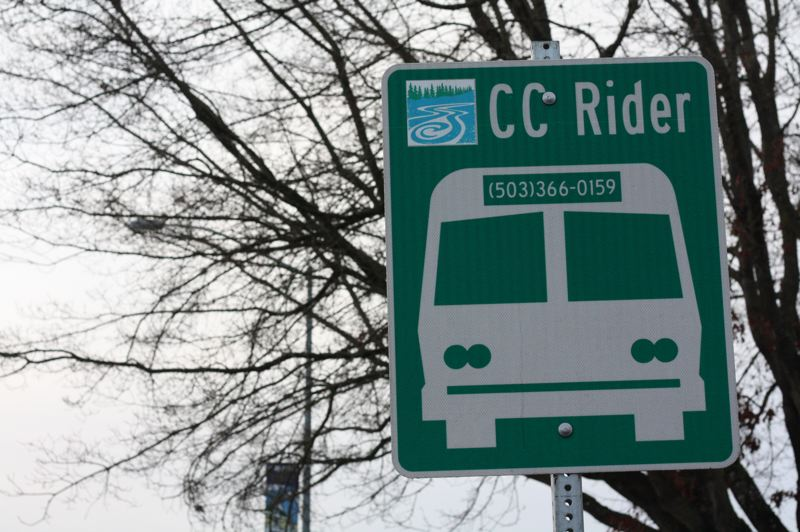 by: SPOTLIGHT PHOTO: KATIE WILSON - A sign for the CC Rider bus stands at the Scappoose Post Office. The Columbia County commissioners recently approved proposed service reductions. Some bus routes will be altered, others will be cut altogether.