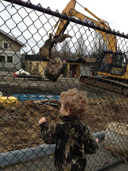 by: LORI HALL - Cody Huth, 2, of West Linn, gets an up-close look at construction crews working to break down boulders they dug up on Wednesday.