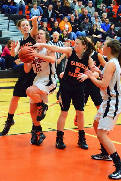 by: JOHN BREWINGTON - Scappoose's Abby Kessi works her way through heavy traffic during last week's game with Yamhill-Carlton. YC won the game in the late going. Kessi and Jenny Vardanega (right) would both make the Cowapa All-League team.