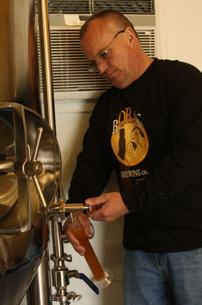 by: POST PHOTO: JIM HART - John Griffith, owner of Boring Brewing Co., samples the brew inside one of his fermentation tanks.
