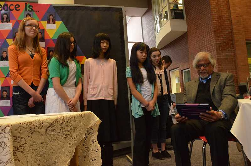 by: TIDINGS PHOTO: VERN UYETAKE - Left, Arun Gandhi watches on an iPad a video that, from left, Clara Adams, Rebekah Pinoli, Theresa Li and Cailee Ito created for him. Above, seventh-grader Miles Noscato reads a poem he wrote. TIDINGS PHOTOS: VERN UYETAKE
