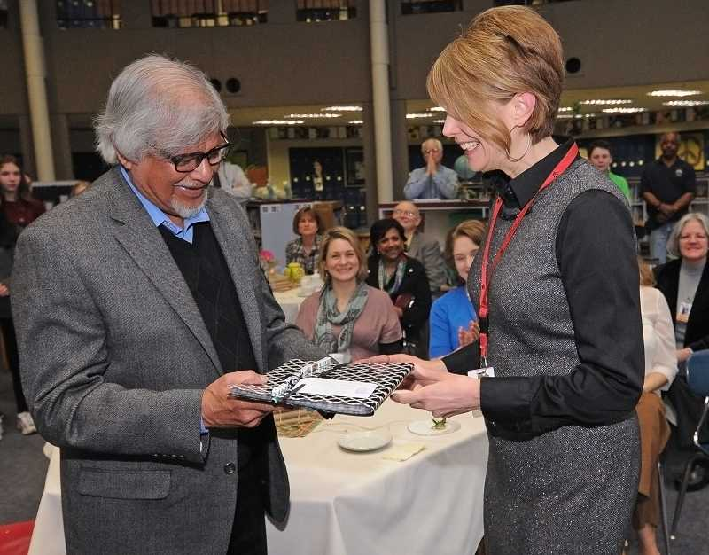 by: TIDINGS PHOTO: VERN UYETAKE - Jaime Etheredge, language arts teacher at Athey Creek, presents Arun Gandhi with an anthology of poems students had prepared.