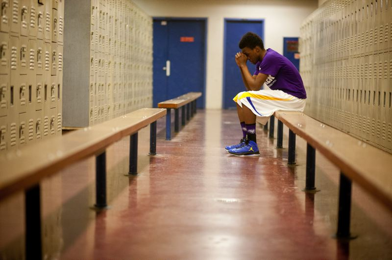 by: TRIBUNE PHOTO: CHRISTOPHER ONSTOTT - Jefferson sophomore basketball player Dario Papa-Vicente takes a moment to pray before the Democrats' Feb. 19 home rivalry match against Benson Tech. One of five high schools sponsored by Nike's Jordan Brand, Jefferson's basketball program is the subject of a documentary project in the works.