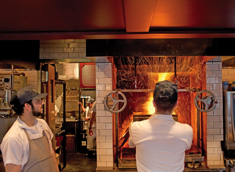 by: TRIBUNE PHOTO: CHRISTOPHER ONSTOTT - Owner Duane Sorenson (right, working the wood-fired oven with a chef), has emphasized the meats and cheeses of Virginia, California, Spain and, of course, Italy, at Ava Gene's on Southeast Division Street.