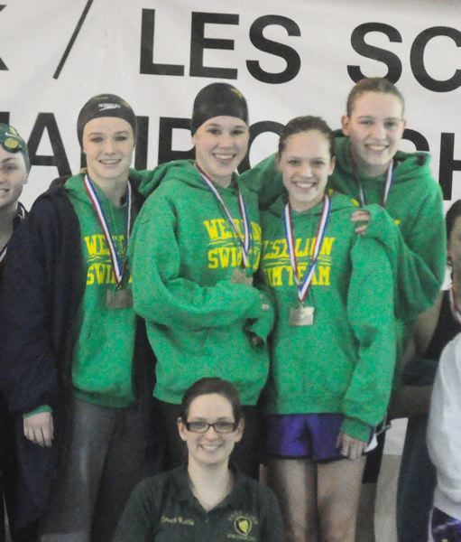 by: MATTHEW SHERMAN - The state championship winning 200 medley relay team of Brie Balsbough, Laura Laderoute, Robin Pinger and Sidney Pinger stand with their medals in front of coach Katie Wilson at the state swim meet.