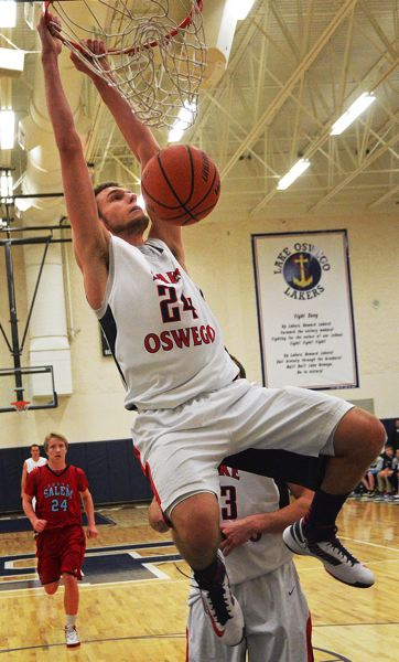 by: VERN UYETAKE - Calvin Hermanson caps a fast break with a dunk in Lake Oswego's playoff win over South Salem on Tuesday.