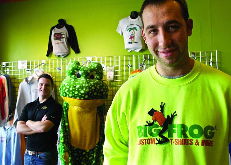 by: TIMES PHOTO: JAIME VALDEZ - Big Frog Custom T-Shirts store owner Ryan Reif and General Manager Ryan Graham show off custom-designed T-shirts at the Murray Scholls Town Center they opened in early 2012.