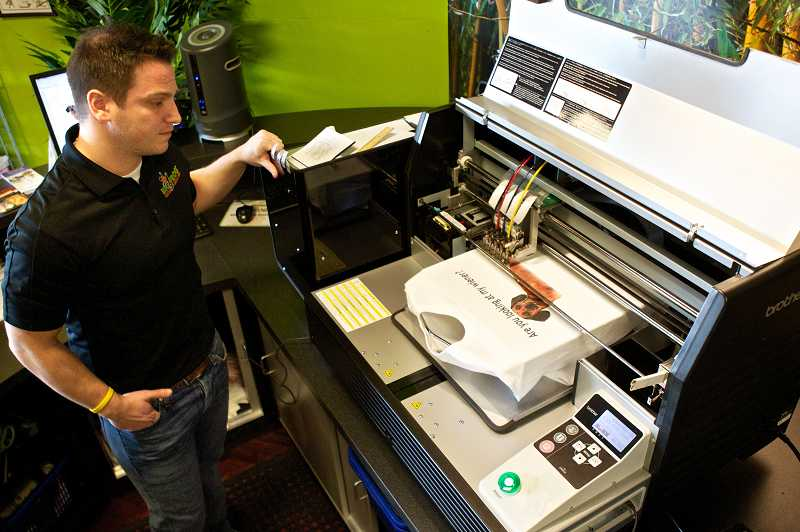 by: TIMES PHOTO: JAIME VALDEZ - Big Frog Custom T-Shirts owner Ryan Reif watches as a high-tech digital printing machine imbeds an image onto a shirt at the stores Murray Scholls Town Center business location, the first Big Frog franchise to open in Oregon.