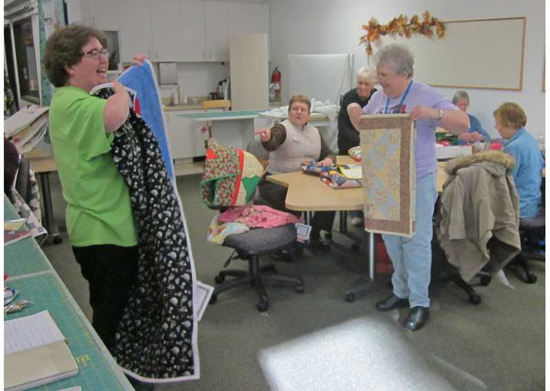 by: BARBARA SHERMAN - THE GOOD WORK NEVER STOPS - Project Linus Portland/Vancouver chapter coordinator Jodene Cook (left) holds up a just-opened blanket for the group to admire at its Jan. 17 regular work session, while Royal Villas resident Dottie Buss points toward it.